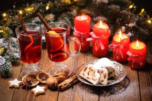 Christmas mulled wine on table with burning advent candles and christmas decorations